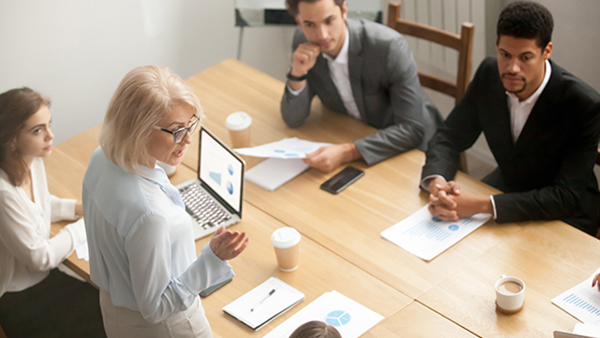 Program manager stands at conference table as employees listen